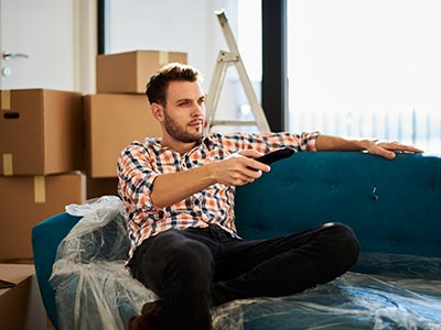 Man sitting on couch with moving boxes behind him