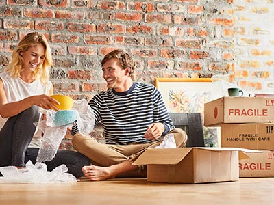 Woman and man smiling and unpacking fragile goods