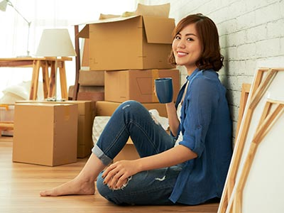 Smiling woman with cup of coffee unpacking apartment move