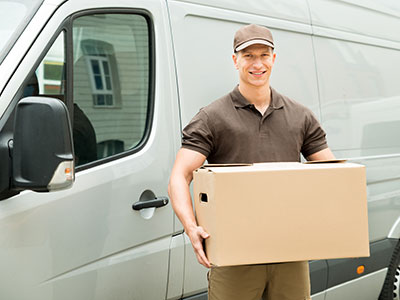 Man smiling in front of van as he delivers package