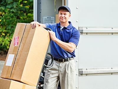 Man smiling with fragile box on dolly in front of transport truck