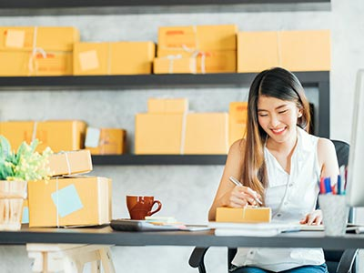 Woman at desk sending packages from her small business