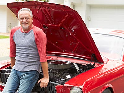 Man in front of red muscle car with hood up