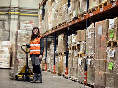 Woman with a high vis jacket on with a pallet jack in warehouse