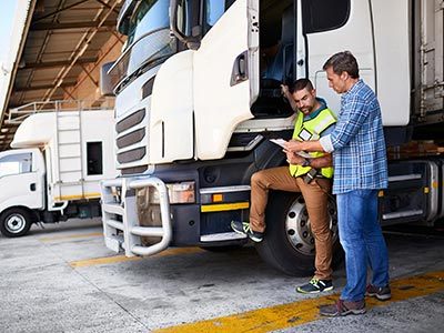 Two white trucks with a truck driver and factory manager