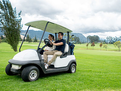 Man and woman driving golf cart on golf course