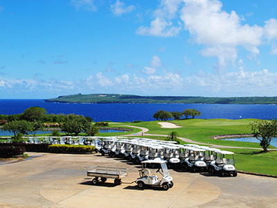 Row of golf carts at a golf course near water