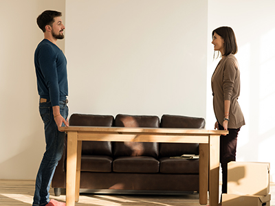 Two people moving a table in front of a couch