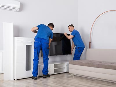 Two movers removing a TV in an apartment