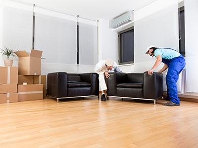 Two movers placing chairs next to moving boxes