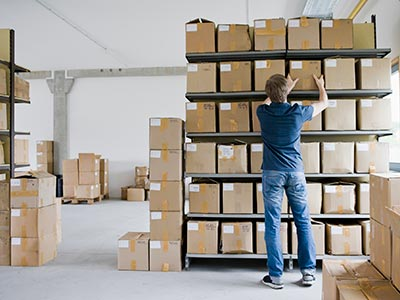 Store owner organizing inventory for shipping