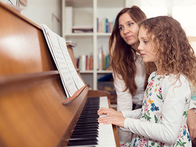 Girl and woman at a piano while girl plays piano