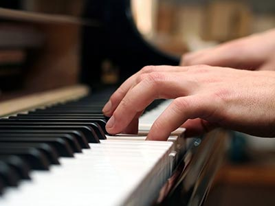 Close up on hands playing piano