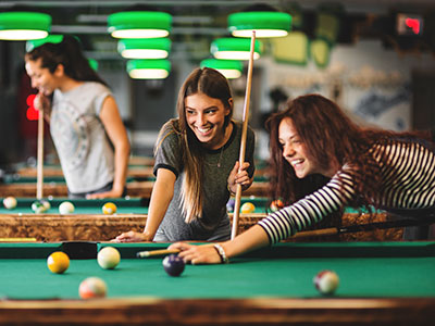 Two women playing pool in a pool hall