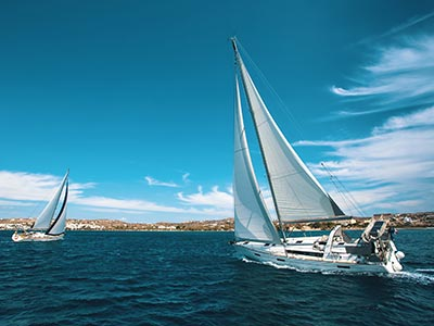 Two sailboats in the water with a blue sky