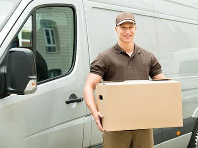 Lieferbote mit einem Paket, der neben einem weißen Packwagen steht
