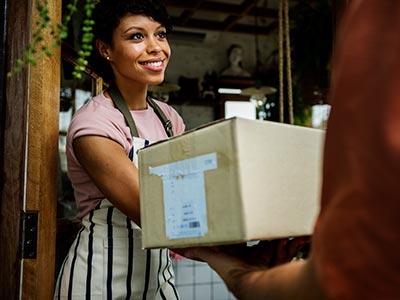 Frau, die Paket an Ihrem Haus empfängt