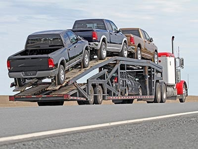 Pickup trucks loaded onto car carrier on highway