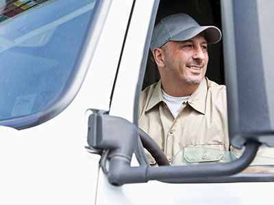 Transporter smiling from drivers seat of truck