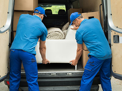 Two white glove movers in blue uniforms unloading a white sofa