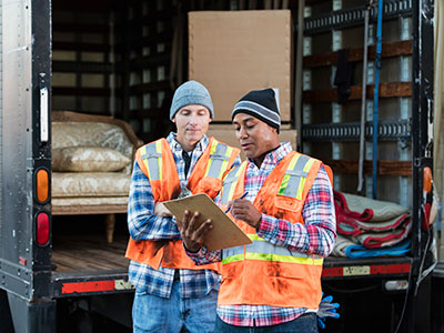 Two white glove movers reviewing their shipment